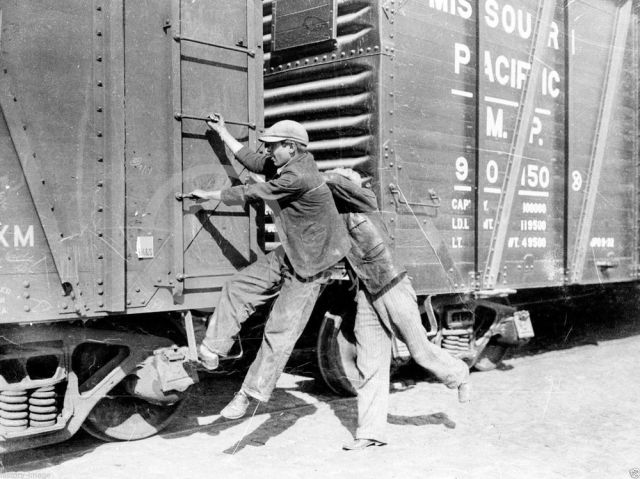 Teenagers hopping on a freight train during the Great Depression, ca. 1930s